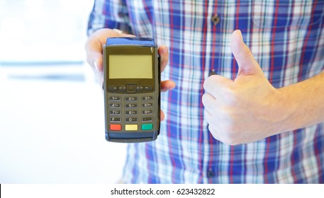 Close-up of male hand using swiping machine to pay credit card and thumbs up. Hand with credit card reader swipe through terminal for payment. Paying by credit card - very good.