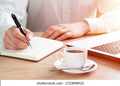 Close-up of male hand writing the to do list in notebook. Businessman at workplace with cup of coffee. Business planning and organisation. Manager working at office with laptop on his desk.