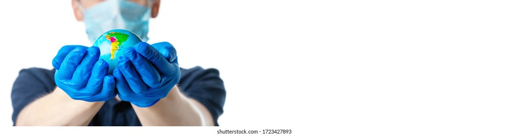 Close-up of male hands in blue medical gloves is holding a small globe that shows South America: Brazil, Argentina and other countries,  a man in a medical mask out of focus, dressed in a blue t-shirt