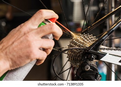 Closeup of male hands cleaning and oiling a bicycle chain and gear with oil spray. Working process
