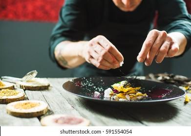 Close-up of male hands cooking molecular dish. Dark background. Molecular cuisine