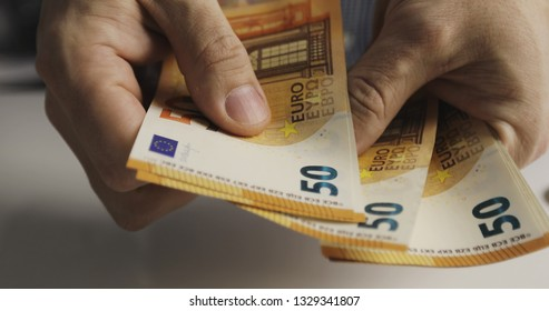 Close-up of male hands counting a pack of fifty euro bills. Currency exchange concept.