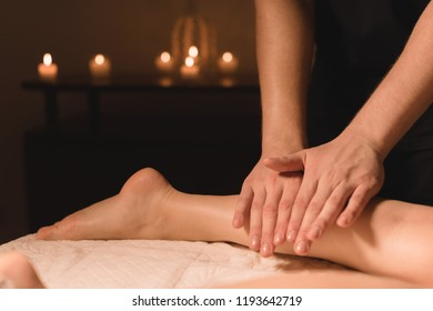 Close-up of male hands doing calf massage of female legs in a dark room with candles in the background. Cosmetology and spa treatments