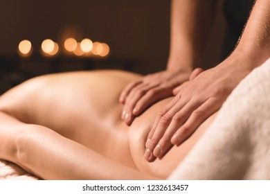 Close-up male hands doing healing massage with oil to a young girl in a dark cosmetology office. Dark key