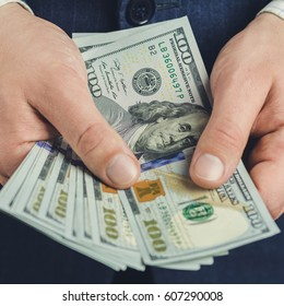 Close-up of male hands hold hundred dollars banknotes, business and finance concept