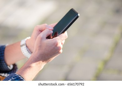 Closeup of male hands is holding cellphone with empty copy space screen for your advertising text message or promotional content. Closely of businessman search information in network with smart phone