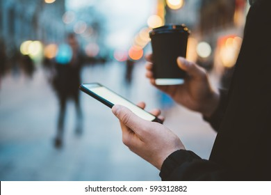 Close-up of male hands holding coffee to go and using smartphone with blank screen at evening outside, visual effects and bokeh light, hipster man walking in the city