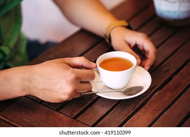 Close-up male hands holding a cup of tea