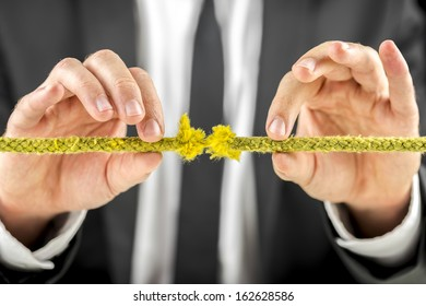 Closeup of male hands holding defective yellow rope.