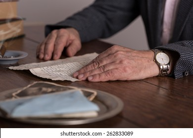 Close-up of male hands holding old letter