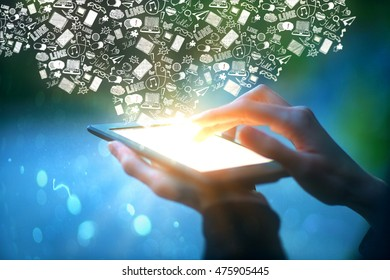 Closeup of male hands holding and touching illuminated screen of digital tablet with abstract communication icons on blue background. Social media concept