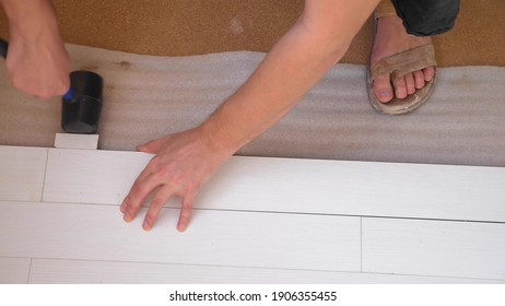 close-up. male hands install white laminate indoors.