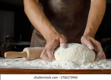 closeup male hands kneading dough