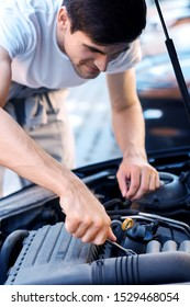 Closeup male hands with metal  wrench are tightening nuts in auto with open hood. Young man driver is repairing automobile on street road. Vehicle breakdown on way. Repairman mechanic is servicing car