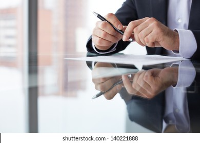 Close-up of male hands with pen over document
