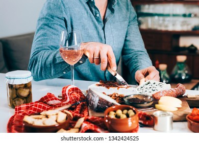 closeup of male hands picking up food with wine. gourmet, tasty, tapas, aperitif concept