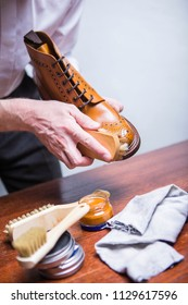Closeup of Male Hands with Polishing Brush for Tan Brogue Derby Boots. Vertical Shot