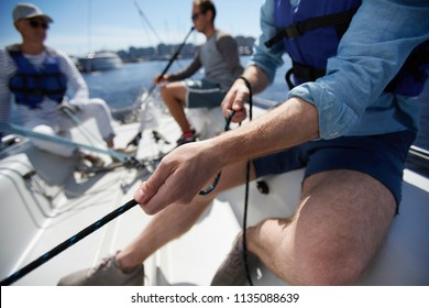 Close-up of male hands pulling rope of sailboat while mooring yacht and sitting with friends on deck