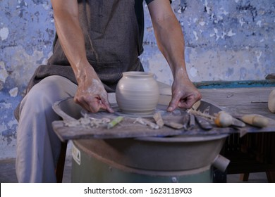 Close-up of male hands sculpt new earthenware with tools and water, man's fingers work with potter wheel.