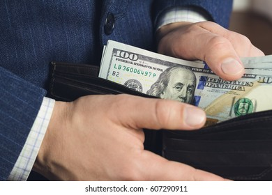 Close-up of male hands taking hundred dollar banknotes from wallet, business and finance concept