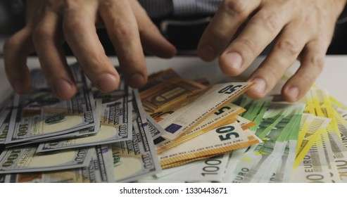 Closeup of male hands taking a lot of money from the table. Denominations: two hundred euros, one hundred euros, fifty euros, one hundred dollars.