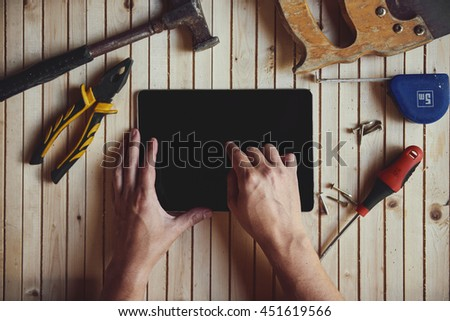 Close-up of male hands touching screen of digital computer pc on worktable with instruments. Concept of handicraft, project and technology.