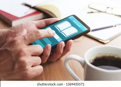 Closeup of male hands touching smartphone screen for reading books at table. 