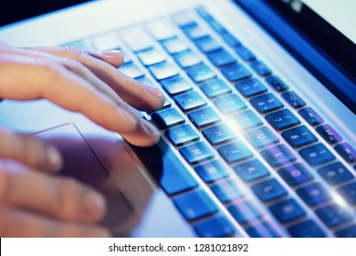 Closeup of male hands typing on laptop keyboard at the office. Visual effects, flares
