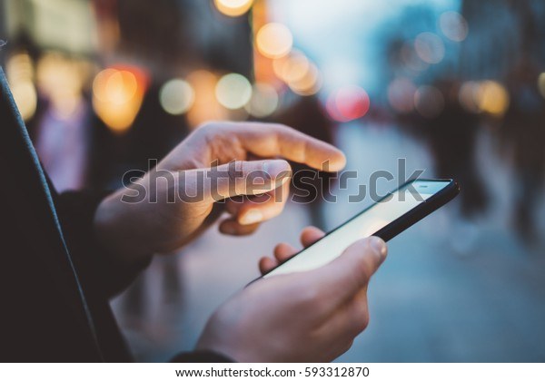 Closeup of male hands typing an sms message via smartphone outside, hipster man enjoying evening walk and using his cellphone, bokeh lights