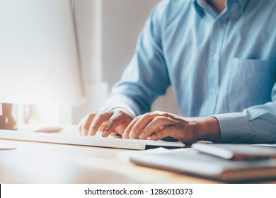 Closeup male hands typing text on a wireless keyboard. Businessman working at the office.