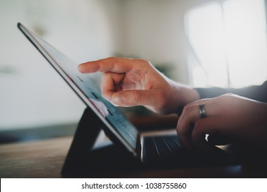 Closeup of a male hands using a digital tablet device in modern loft with big light windows, businessman typing on touch screen of a portable computer while working in office, technology concept
