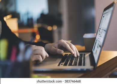 Close-up of male hands using laptop at office, man's hands typing on laptop keyboard in interior,, side view of businessman using computer in cafe