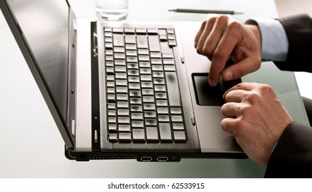Close-up of male hands using laptop on desk