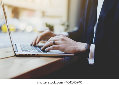 Close-up of male hands using modern laptop in coffee shop, businessman in suit working on notebook computer in interior, flare light
