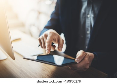 Close-up of male hands using modern digital tablet and computer at office, frontal view of businessman hands typing text information on touch screen of tablet pc, modern workspace at vintage loft
