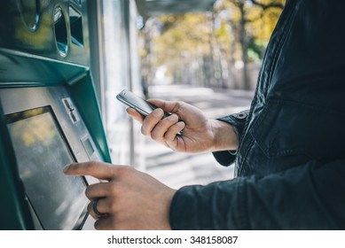 Closeup of male hands using smart phone while typing on ATM, bank machine