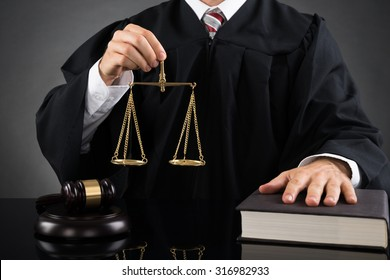 Close-up Of Male Judge Holding Golden Weight Scale At Desk