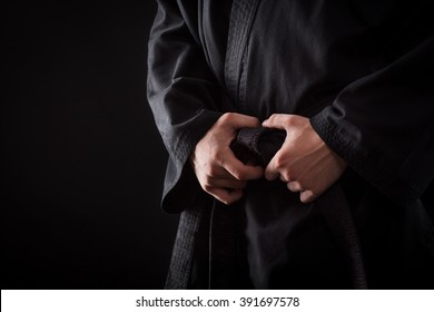 Closeup of male karate fighter hands on the knot of black belt