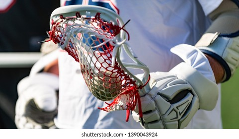 Close-up of a male lacrosse player holding his stick. The player is wearing lacrosse equipment including gloves and is holding the lacrosse ball.