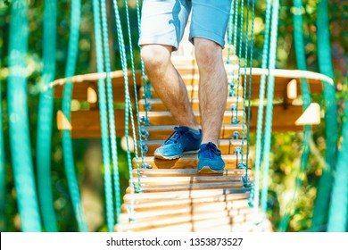 Closeup male legs in blue sneakers walking and keep balance on rope bridge on high trees in park. Rope park with different obstacles and ziplines. Extreme rest and summer activities concept.