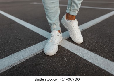 Close-up of male legs. Fashionable young man stands on the asphalt road in leather stylish white sneakers in trendy blue jeans. Seasonal men's shoes. Street casual style.