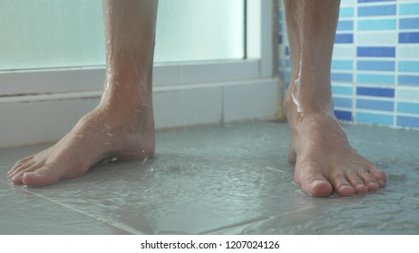 close-up of male legs in the shower. the young man takes a shower.