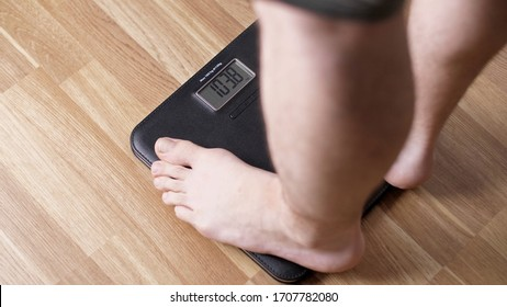 Close-up male legs stand on the scales. Fut man on scales measure weight. Human barefoot measuring weight loss or overweight during quarantine.