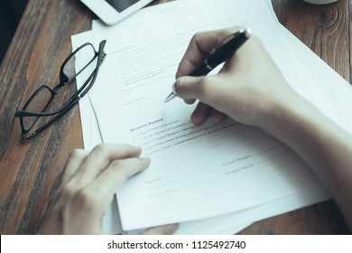 Close-up of male manager working with documents. He writing in paper. Eyeglasses, tablet, mug with coffee on table. Businessman analyzing report. Paperwork concept