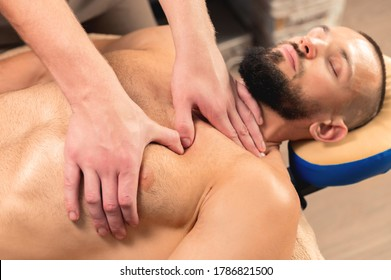 A close-up male masseur does a sports massage of the pectoral muscle to the client athlete in a professional massage salon. The concept of pectoral muscle and breast muscle health