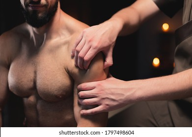 close-up male masseur does a sports shoulder massage to a muscular male athlete in a room with a contrasting dark light. Professional sports massage