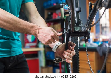 Closeup of male masters' hands repairing the chain mechanism of the bicycle in a special store