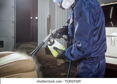 Close-up of a male mechanic with a blue prism and protective gloves makes a dry-cleaning of the car's beige car seat with a sprayer in the car service area