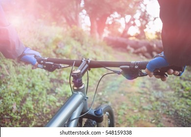 Close-up of male mountain biker riding bicycle in forest