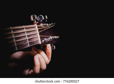 closeup male musician hands tuning acoustic guitar strings, isolated on black